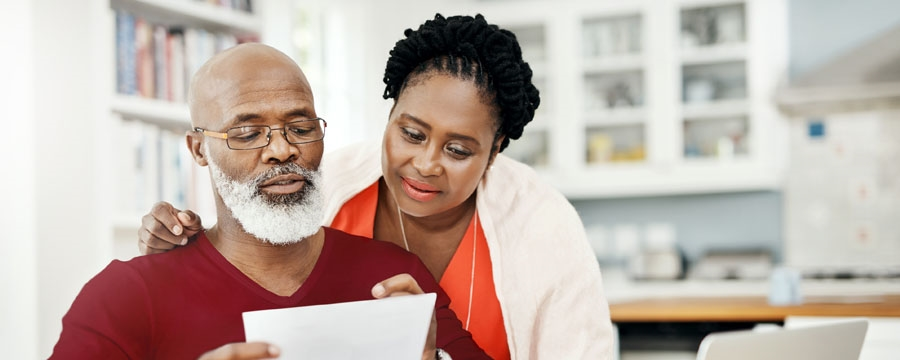 Couple looking at a financial statement together at their kitchen table in their home.